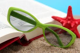 book with sunglasses in the sand