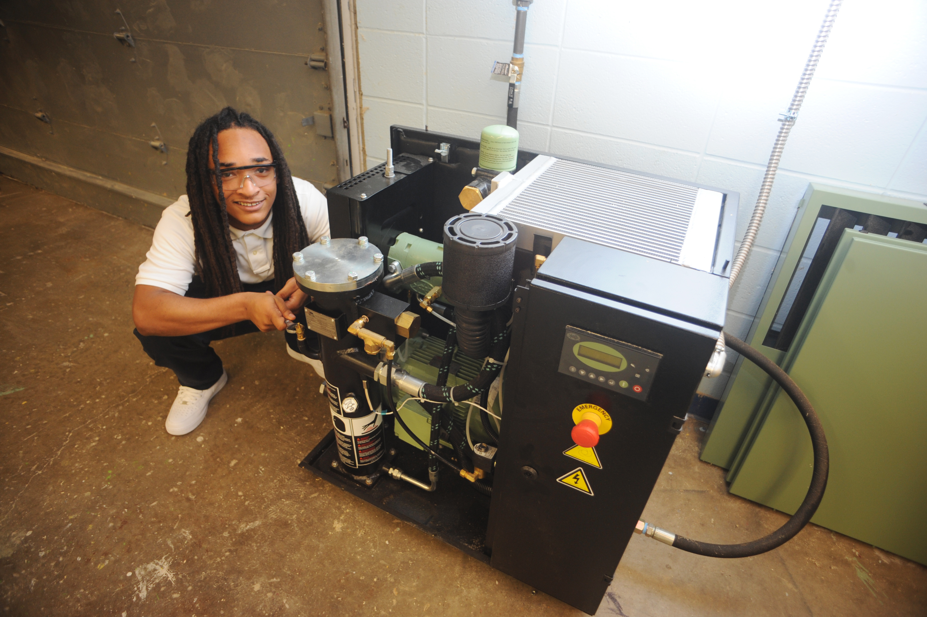 high school student smiles at camera while working on air compressor
